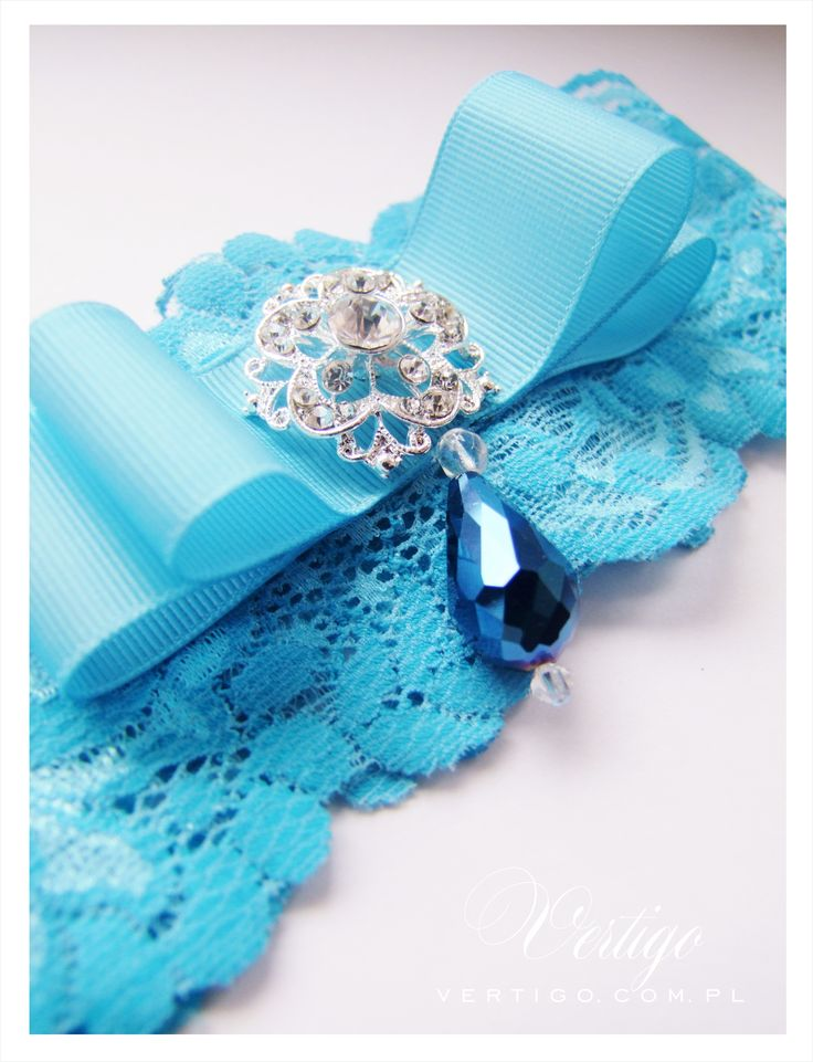 handmade blue wedding garter with lace, pearls, bow, feathers and swarovski crystals, source: www.vertigo.com.pl