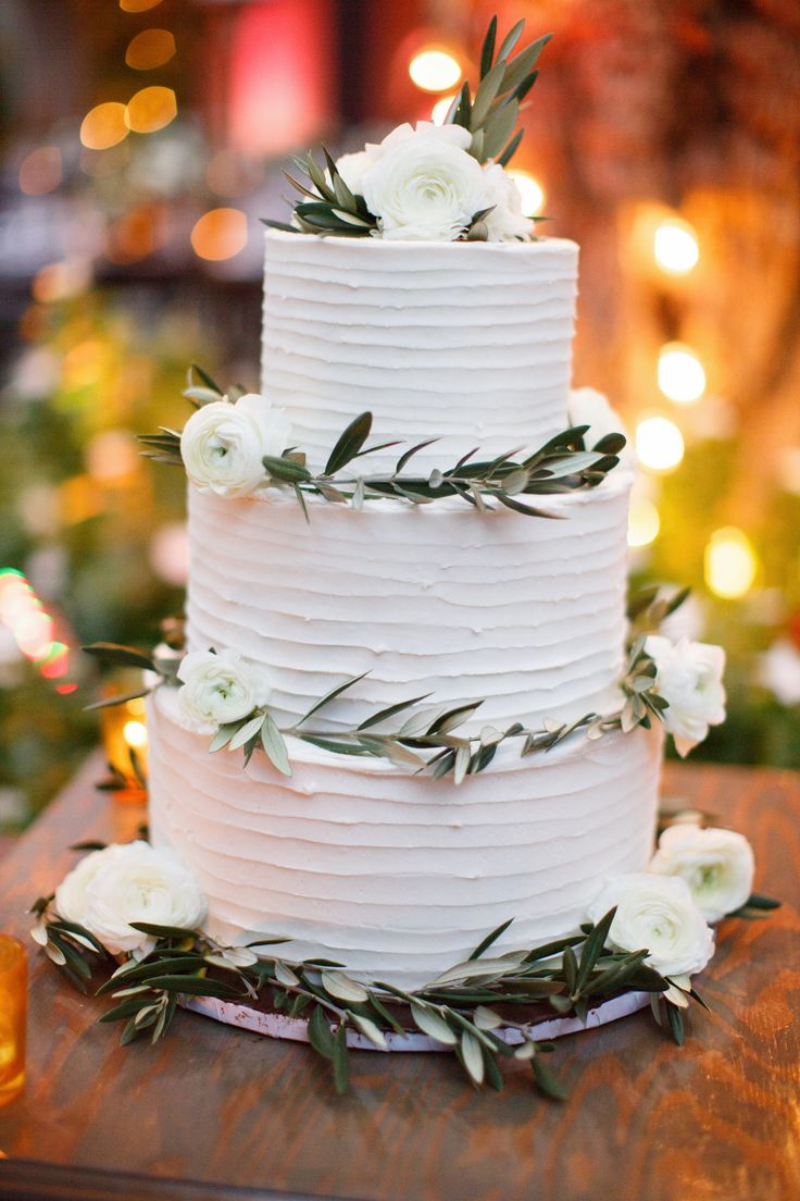 Simply Elegant White Wedding Cake With Olive Leaf Greenery And Petite Roses Photographed