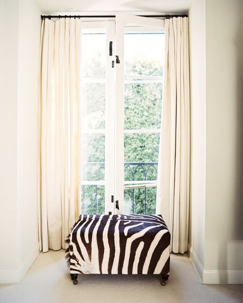 """""""White room."""" Interior. French doors. White curtains. Zebra-covered ottoman. Hollywood Regency Furniture."""