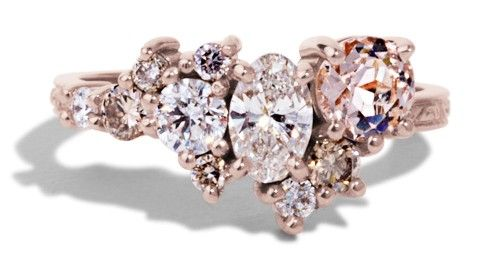 This custom Cluster Ring features a 5mm round morganite, .40ct oval diamond, .17ct diamond, .03ct diamond, two .06ct champagne diamonds, and three .02ct champagne diamonds. The polished 14kt rose gold shank is engraved with an intricate pattern.
