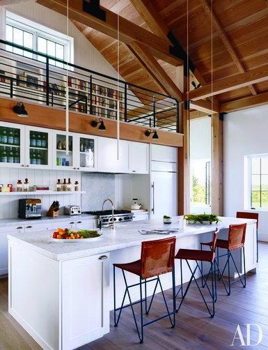The kitchen of a Martha's Vineyard residence designed by Ariel Ashe and Reinaldo Leandro features a Sub-Zero refrigerator, a Wolf range, and Dornbracht sink fittings; the minimalist pendant lights are by Davide Groppi, the Bernard-Albin Gras sconces are by Design Within Reach, and the barstools are by Garza Marfa | archdigest.com