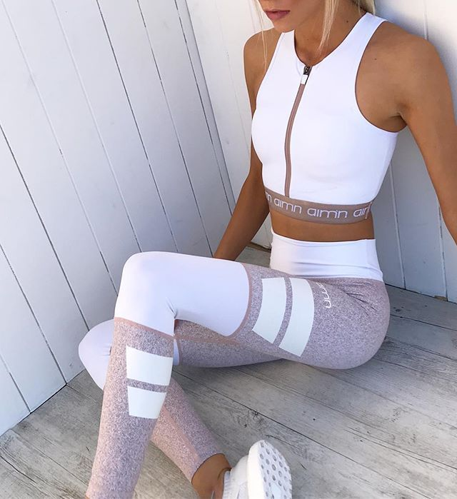 White co-ord workout outfit with cropped zip front top and striped colorblock le…