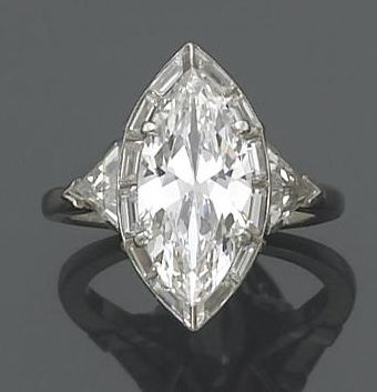 A diamond and platinum solitaire ring  centering a marquise-cut diamond within a surround of baguette-cut diamonds, completed by triangular-shaped diamond shoulders and a plain mount; marquise-cut diamond weighing an estimated: 2.70 carats; remaining diamonds weighing an estimated: 0.85 carats.