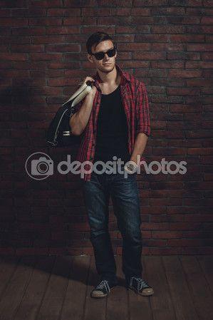 Hombre joven inconformista con gafas de sol casual ropa desabrochada camisa y denim jeans con bolso sobre pie hombro cerca de muro de ladrillo de la mano en el bolsillo mirando lejos — Imagen de stock #67259995