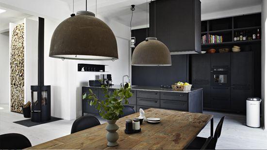 Dark kitchen in an old pen factory - table, pendant lights, crisp white walls & ceilings