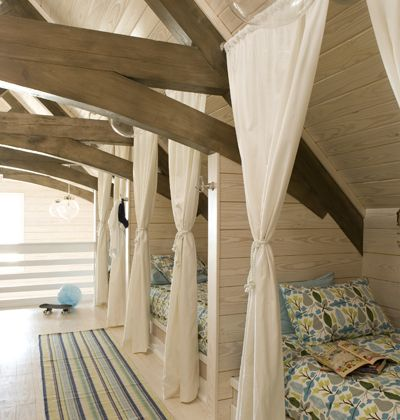 Built-in beds in a row can take advantage of an otherwise awkward space in the attic & is perfect for sleeping multiple kids in one room. The children can personalize the area around their bed nooks.