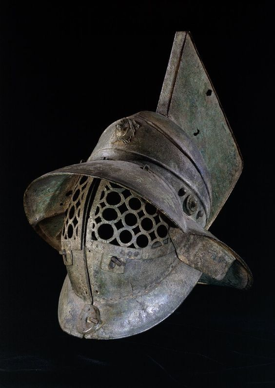 Helmet - bronze. Period/Culture: Roman. Date 1stC. Description Bronze gladiator's helmet. It has a grille of linked circles to protect the face, and a broad brim to protect the back and sides of the head. At the front of the helmet is a medallion of Hercules.: