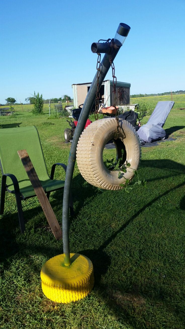 Repurposed from lawn mower tires, trampoline pole, & old swing set chain into a planter