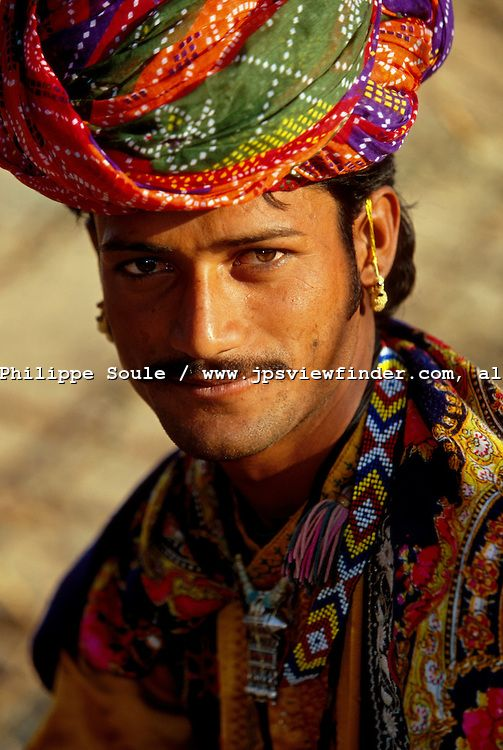 He wears these colors so well.  Kalbeliya Gypsy, Nomadic People of the Rajasthan Desert, Pushkar, India..Dressed in full regalia, Suresh, the Kalbeliya Gypsy group leader is ready to play his tablas drums..The Kalbeliya Gypsy people are known as the snake charmer caste. The women are skilled dancers and are accompanied by men playing percussion and wind instruments. The Kalbeliya were once hired to entertain great kings and maharajahs.