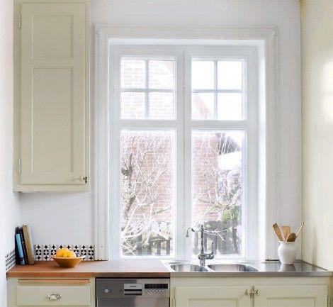 Bevarade gamla fönster med spröjs och linoljemålad köksinredning.
