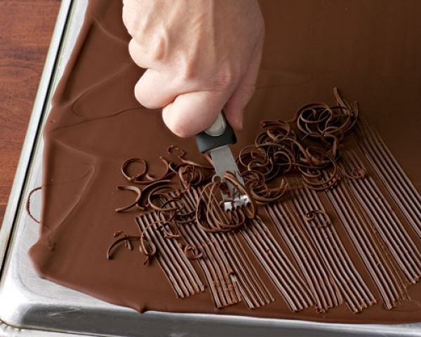 Chocolate Curls - Use a large offset spatula to spread melted chocolate evenly over the back of a rimmed baking sheet to create a thin coating. Let stand at room temperature until it loses its sheen, 10 to 20 minutes; then refrigerate until the chocolate is set but not hard, 5 to 10 minutes. Pull a citrus zester through the chocolate to create narrow curls.
