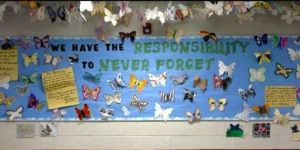 """Eighth-graders created butterflies that are decorating a bulletin board at Thomas Jefferson Middle School after reading """"I Never Saw Another Butterfly"""" as part of their study of the Holocaust."""