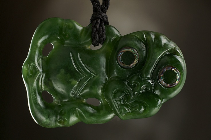 Unikat Jade Tiki Schmuck Anhänger.    Verarbeitet aus neuseeländischer Jade im traditionellen Tiki Stil.  Designed by Ewan Parker.    Dem Träger dieses Tiki Symbols wird die Klarheit des Gedankens, tiefe Loyalität sowie das große innere Wissen nachgesagt.