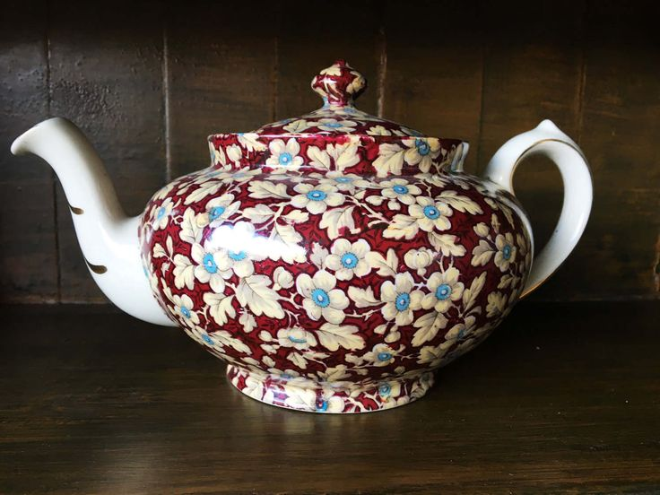Charming 1950s Lord Nelson Royal Brocade teapot.  Its always teatime with this delightful midcentury teapot featuring a vibrant Maroon/red color and turquoise flowers.  The spout is detailed with gold-tone stripes.  Dimensions: 7 tall, 5 wide, 5 depth  Condition: Vintage, excellent
