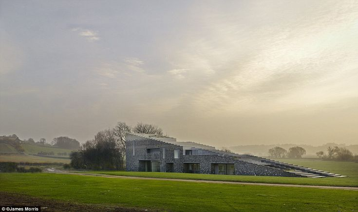 This wedge-shaped house in Buckinghamshire has been awarded House Of The Year in the prestigious Royal Institute Of British Architects (Riba) awards.Commissioned by Lord Rothschild for use by his family, Flint House rises out of the ground with roofing that disappears into the sky
