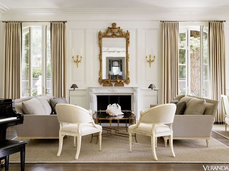 Custom sofas in a Great Plains fabric, Hutton Home; pillows in a Fortuny fabric; cocktail table, Dennis & Leen; floor lamps, Restoration Hardware; sconces, Marvin Alexander, Inc.; curtains in a Clarence House linen; rug, Merida, with a Kravet trim.
