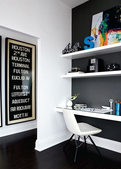 Dark charcoal feature wall, white shelves colourful art and decor + modern and stylish workspace.