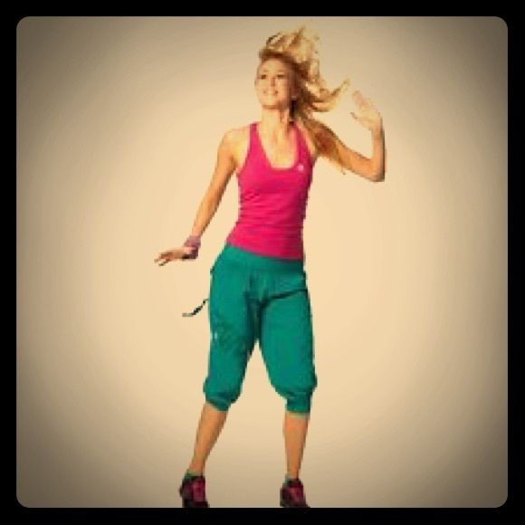 """Feelin it cargo Capri - ZUMBA Fitness (peacocks) Draggin' that wagon behind you to class today? Slip into the Feelin' It Cargo Capri and feel the instant charge of energy. Watch heads turns as you hit the floor in the ultimate Zumba® wear pants! Make 'em do a double take while you break it down and let your tassels fly! Splatter-paint inspired design """"Feel the Music"""" printed on pocket tassels Loose, relaxed fit MADE WITH LOVE AND: 100% nylon Additional inspiration comes complimentary ZUMBA…"""