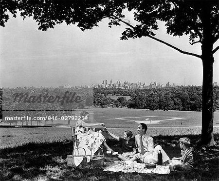 1940s FAMILY PICNICKING UNDER A TREE IN FAIRMONT PARK WITH SKYLINE OF PHILADELPHIA PA ON HORIZON