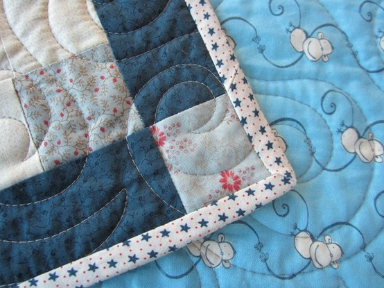 A close up of the corner detail, binding and backing of Teddies Quilt.