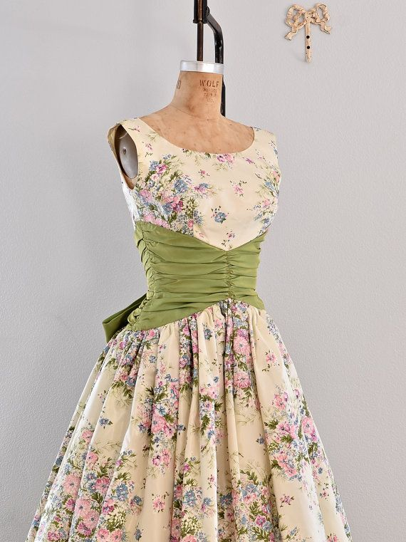• vintage 1950s floral print dress  • scoop neckline  • green cummerbund waist and tail like bow at the back  • full skirt lined with tulle and paper like material for added fullness  • back metal zipper closure    fabric: acetate  fits like: xxs xs small  condition: excellent ✂- - - - - Measurements    length: 43 inches  bust: 32 inches  waist: 24 inches