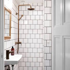 Black and white industrial bathroom and shower with brass details by ApartmentStudios