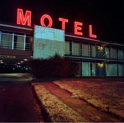 Motel with neon sign at night. Photo by Poppy de Villeneuve