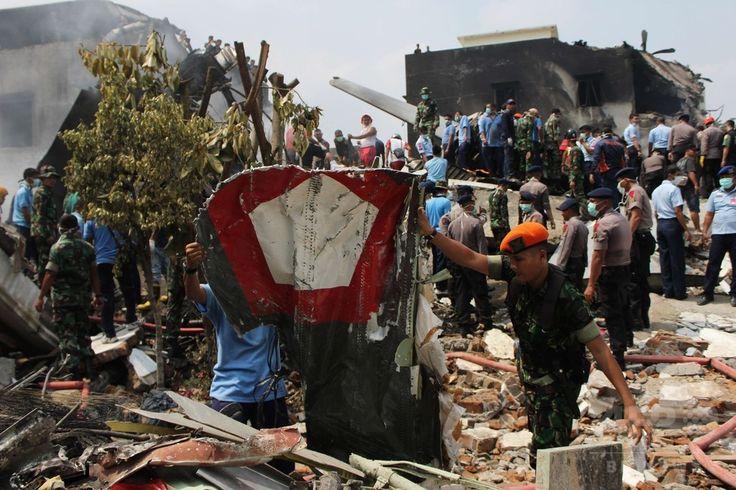 インドネシア・スマトラ島メダンで、空軍輸送機が墜落・炎上した現場で作業にあたる兵士ら(2015年6月30日撮影)。(c)AFP/ATAR ▼1Jul2015AFP|インドネシア軍機墜落、死者141人に http://www.afpbb.com/articles/-/3053313