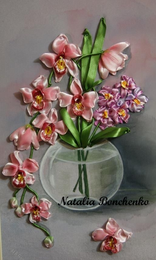 Ribbon embroidery of an orchid. The petals fade from white at the edges inward to a medium blushing pink and have red and yellow centers-