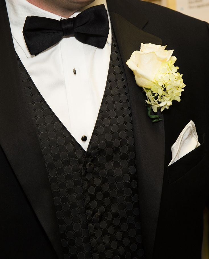 Classic groom style: black tuxedo with patterned vest and rose boutonniere (Michael Chadwick Photography)