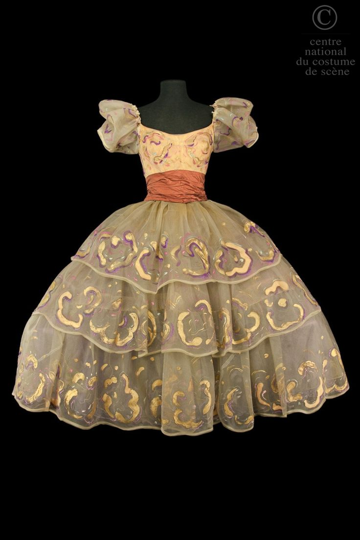 Artistes:  Madeleine Lafon  Descriptif costume:  Robe crinoline avec bustier orange recouvert de crin peint or, rose et violet, petites m...