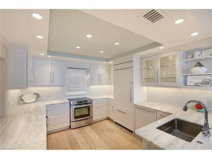 White cabinets, onyx countertops, driftwood floors, glass backsplash