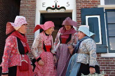 Vrouwen in kassekijntje (korte jas), de middelste twee in ongetrouwde dracht, de rechter in lichte rouw.