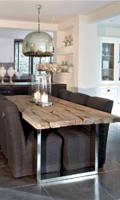 Modern rustic dining room area. Love the wood plank table and statement light fixture.