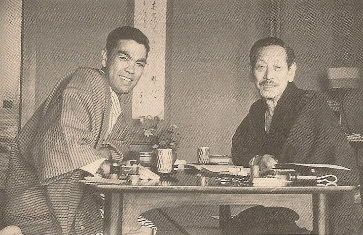 Kayano Shigeru with Linguist Kindaichi Kyōsuke. Kayano Shigeru (1926-2006) was an inheritor and preserver of Ainu culture. He was a collector of Ainu folk utensils, teacher of the prominent Japanese linguist Kindaichi Kyōsuke, and recorder and transcriber of epics, songs, and tales from the last of the bards.