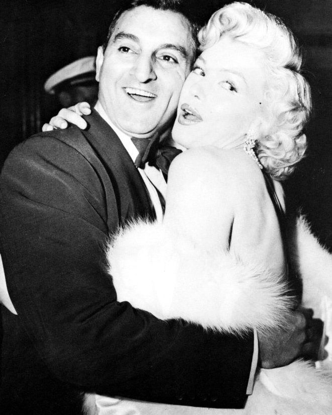 Marilyn Monroe and Danny Thomas share a friendly clinch between curtain calls of a benefit show at the Shrine Auditorium in Los Angeles 1953.
