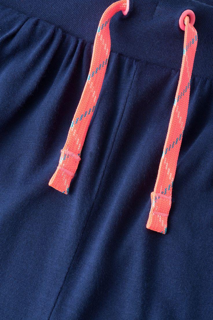 Details:  -De luchtige snit met lager kruis en de lichte jersey die soepel valt, maken deze broek perfect voor warme dagen.  -Hij is gemakkelijk aan te trekken dankzij de elastische band. -Voorop is hij versierd met neonkleurige ringen en koordjes (zonder functie). -Het wijde model heeft plooitjes bij de band. -Met steekzakken aan de voorkant.