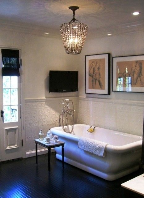 Freestanding tub, TV, glossy wood espresso stained floors, ivory walls. This is my dream bathroom.