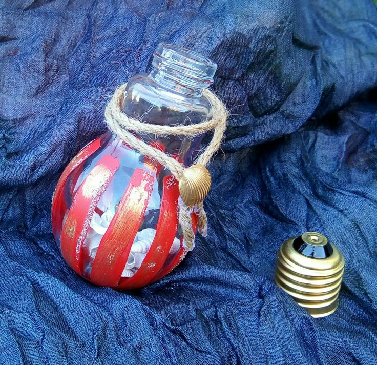 Lampadina in vetro decorata con conchiglie verniciate bianco, vernice esterna rossa e oro, con spago. Soprammobile o da appendere all'albero!