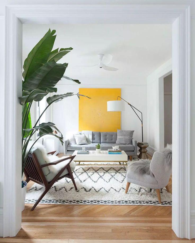 Soggiorno scandinavo in colori bianco e grigio ed un quadro di grandi dimensioni colore giallo sole che dona vivacità e personalità all'ambiente - Idee soggiorni moderni
