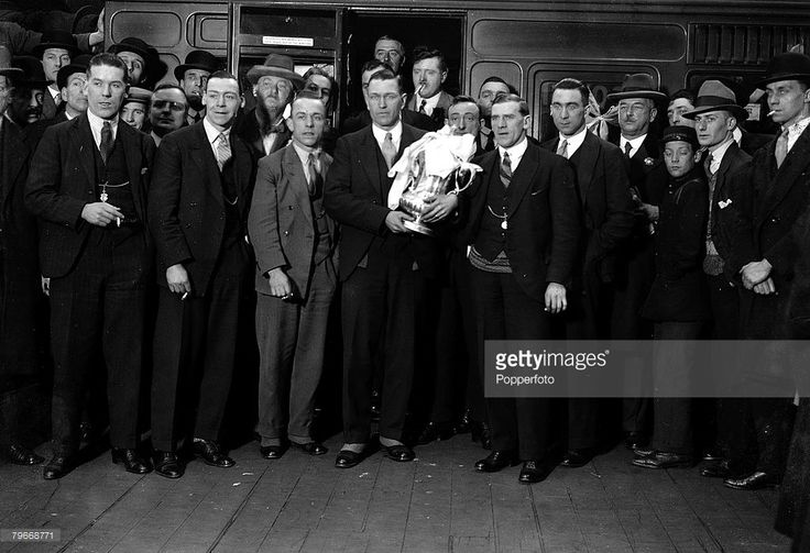 Football, London, England, F,A,Cup Final 1928, Blackburn Rovers 3 v Huddersfield Town 1, Rovers+ victorious players leave London for home after winning the F,A Cup, Skipper Harry Healless holds the trophy surrounded by his team mates at Euston Station