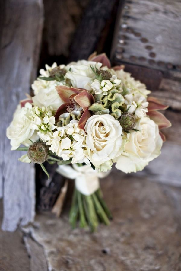 Pretty bouquet of cream with a touch of rusty brown - roses, stocks, celosia, cymbidium orchids and scabious seed heads