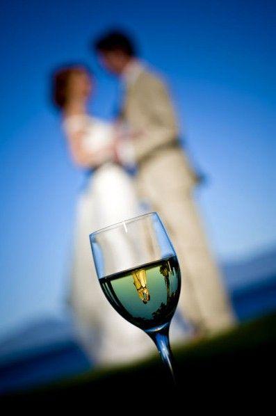 Esta foto é de tirar o fôlego! O ângulo deixa a foto dinâmica e o reflexo na taça torna a foto extremamente artística! Mais ideias para fotos de casamento aqui!