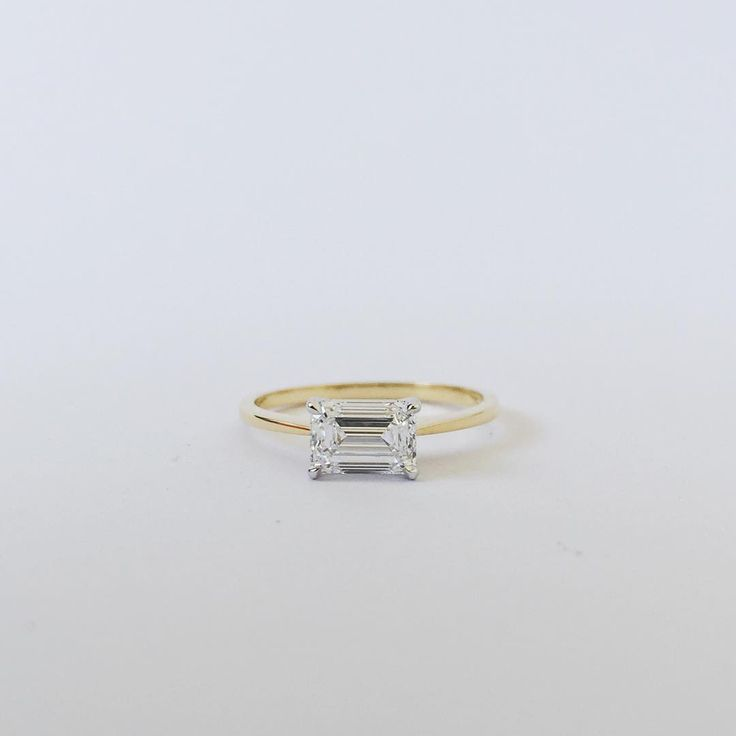 """""""Recent custom engagement piece.  A step cut emerald diamond set east to west on a tapered fine band.  The studio will reopen next week - very excited to…"""""""