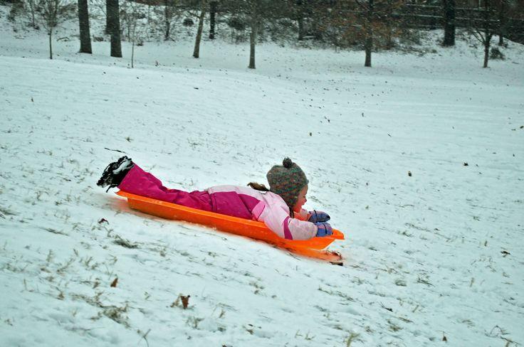 Seorang anak bermain seluncur di salju yang turun di Washington D.C.