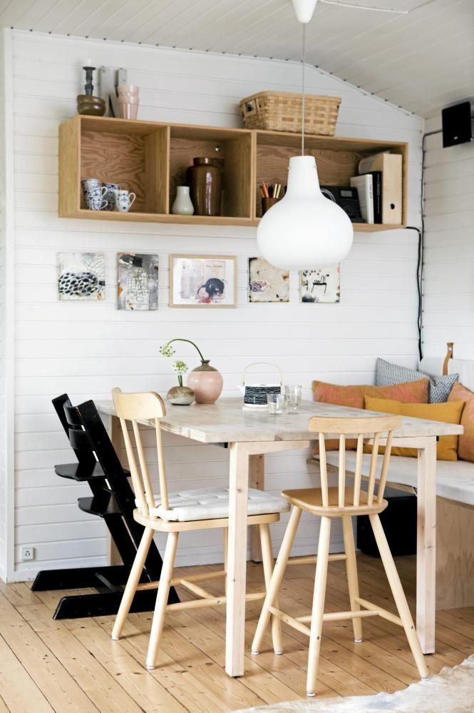 Benken inntil veggen strekker seg fra spisestuen og helt inn til stuen. Sommerhuset har derfor både sofa og spisestuebenk i ett. Resten av stolene er i ulike former og farger. En trehylle på veggen er både dekorativ og praktisk.