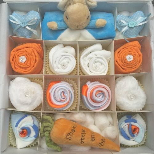 This cupcake gift set will be adored by any little baby boy! Featuring a gorgeous Peter Rabbit comforter and carrot rattle! This set is also available in Pink and neutral too. Comes presented in a large white or ivory gift box tied in a bow with orange and blue ribbon Cupcake