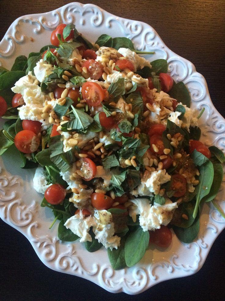 Vasket og renset grønnkål masseres i litt olivenolje. Blandes med like deler Babyspinat. Pumpernikkel deles i skiver, og legges på en bakeplate. Ha over litt olivenolje, og et stykke chevre, og ha det i ovnen i ca 10 minutter til chevren har blitt myk. Del persimon i båter, og ha disse over salaten sammen med granateple og ristede pinjekjerner. Varm chevre legges over salaten. Ha over litt salt, pepper og søt balsamico (eller honning).