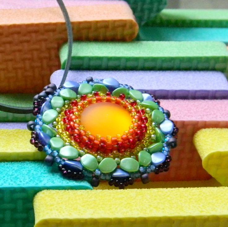 Daisy+Duhový+náhrdelník+je+vyrobený+obšitím+skleněného+kabošonu+kvalitním+japonským+TOHO+rokailem+v+různých+velikostech+a+voskovanými+korálky+Pohanka.+Vše+je+v+barvách+duhy.+Kabošon+je+matně+oranžový+se+sametovým+povrchem.+Přívěšek+je+zavěšen+na+kožené+ploché+šňůrce+tmavě+zelené+barvy+a+je+podšitý+velmi+příjemným+semišovým+podkladem+Ultra+Suede.+Délka...