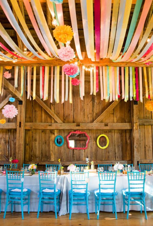Colorful barn reception with ribbon and tissue poms.